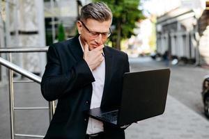senior affärsman håller öppen bärbar dator och uppmärksamt tittar på skärmen vidrör hans ansiktsbild foto