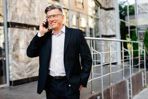 leende senior affärsman pratar i mobiltelefon utomhus. - bild foto