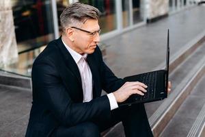 senior affärsman sitter på trottoaren, håller en bärbar dator och skriver. - bild foto