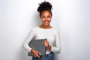 ung flicka håller bärbar dator medan du står i studion foto