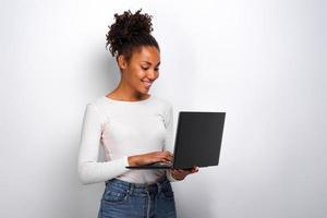 porträtt av flicka som håller bärbar dator och ctyping tittar på skärmen foto