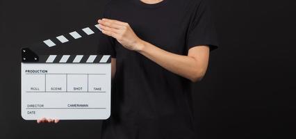 kvinnlig modell håller klaffbräda eller filmskiffer i studioskytte. det används i videoproduktion och bioindustri på svart bakgrund. foto