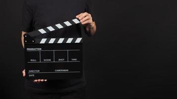 kvinnan håller klaffbräda eller filmskiffer i studioskytte. den används i videoproduktion och bioindustri på svart bakgrund. foto