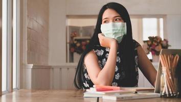 trött kvinna som bär en medicinsk mask tittar ut genom fönstret, med bärbar dator och brevpapper på bordet. foto