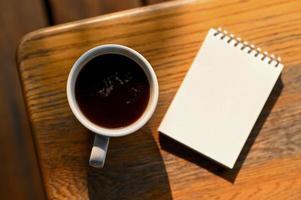 kaffe och en anteckningsbok på bordet, toppvy skott. foto