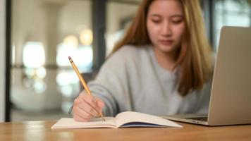 närbild skott av asiatisk tonåring skriver på anteckningsbok med bärbar dator på skrivbordet under online -klass, studerar online hemma. foto