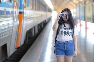 en tonårskvinna som håller en kamera vid en tågplattform. foto