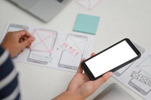 ux, ui -designer som håller en smartphone och utarbetar en ny design. foto