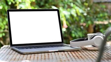 mockup bärbar dator tom skärm och hörlurar med kaffemugg på järnbord, grön trädbakgrund. foto