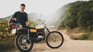 en tonårspojke och en klassisk enduromotorcykel på en stenig väg. foto