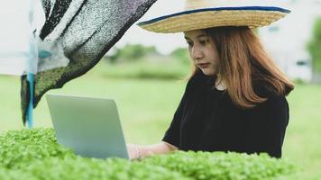 en ny generation kvinnliga bönder med bärbar dator i hydroponikplantagen i växthus, smart gård. foto