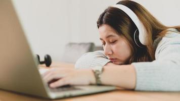 asiatisk kvinnlig student som sover medan han studerar online med bärbar dator och hörlurar. foto