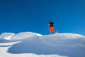 en man alpin skidåkare klättra på skidor och sälskinn i alpinkam foto