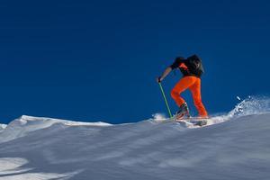 en man alpin skidåkare klättra på skidor och sälskinn foto