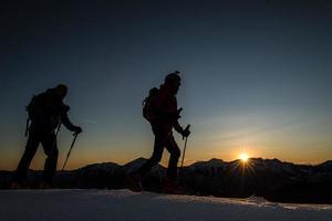 skidåkare klättrar berg med skidor på kvällen vid solnedgång foto