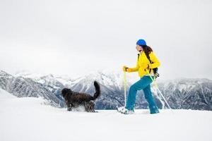svart hund med en tjej på promenad med snöskor i bergen foto