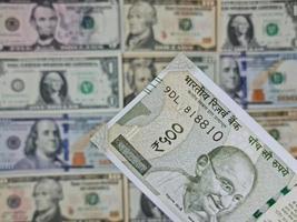 tillvägagångssätt för indisk sedel och bakgrund med amerikanska dollarräkningar foto