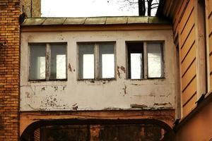 tre gamla rostiga fönster i vita korridorer som överbryggar byggnader foto