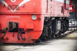 rött tåg som står på järnvägen en solig dag foto
