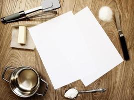tomma pappersark på träbord med bakverktyg och ingredienser foto