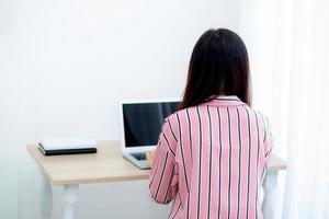 ung asiatisk kvinna som arbetar på bärbar dator som sitter i vardagsrummet. foto