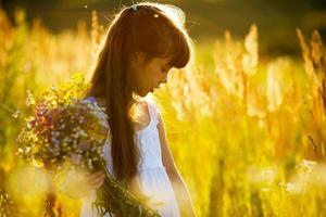 flicka med en bukett vilda blommor foto