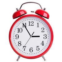 rund väckarklocka visar fem minuter till tre foto