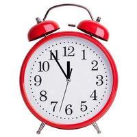 röd väckarklocka visar fem minuter till tolv foto