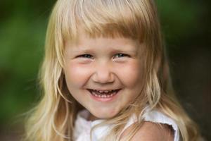 glad liten blond tjej ler glatt foto