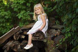 liten flicka som sitter på gamla brädor foto