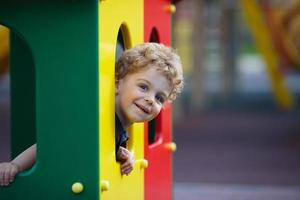 liten pojke gömmer sig på lekplatsen foto