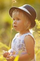 liten blond tjej i klänning och hatt foto