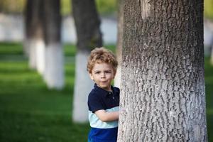 liten pojke gömmer sig bakom ett träd foto