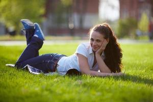 ung kvinna ligger på en gräsmatta foto