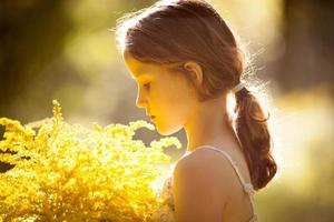 liten flicka som står med en bukett blommor foto