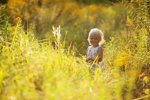 liten vacker flicka i en klänning foto