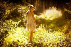 den lilla flickan är i en skog foto