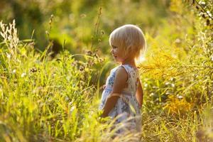 liten blond flicka i klänning bland vildblommor foto