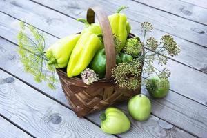 grönsaker i korgen. en korg med paprika, tomater och dill står på en träbakgrund. foto
