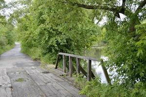 vackert stående gammal träbro över floden i färgad bakgrund foto