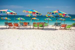 strandstol under paraplyet av färgglada på stranden phuket, thailand foto
