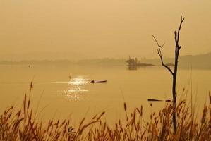 vacker utsikt skuggor ljus lång-tailed båt soluppgång i dam srinakarin nationalpark kanchanaburi, thailand foto