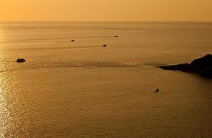 skönhetslandskap med gyllene solnedgång ovanför havsbakgrunden foto