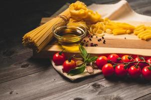 välsmakande aptitretande italienska spaghetti pasta ingredienser för kök med tomat, ost parmesan, olivolja, fettuccine och basilika på träbrunt bord. mat italienskt recept hemlagat. toppvy foto
