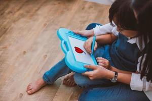 asiatisk mamma som lär söt pojke att rita rött hjärta ombord med färgpenna. tillbaka till skolan och utbildning koncept. familj och hem söt hem tema. tema för förskolebarn. ovanifrån vinkel foto