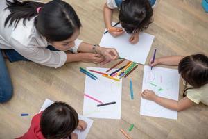 grupp förskoleelev och lärare som ritar på papper i konstklassen. tillbaka till skolan och utbildning koncept. människor och livsstilar tema. rum i barnkammaren foto
