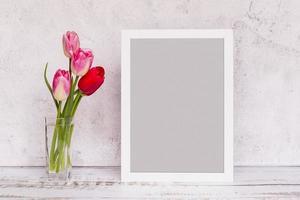 färska blommor i vas med ram foto