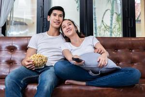 asiatiska par som tittar på tv och äter popcorn tillsammans i soffan i sitt hem. människor och livsstil koncept. gott hem och aktivitetstema foto