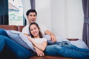 asiatiska unga par som kopplar av på soffan. älskare och par koncept. smekmånad och bröllopstema. interiör och dating tema foto