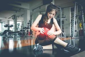 asiatisk kvinna skador under träning på knä i fitness gym. medicinsk och hälsovårdskoncept. tränings- och träningstema foto